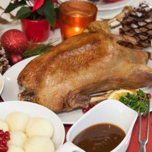 Festlich gedeckter Tisch mit Entenbraten und Beilagen